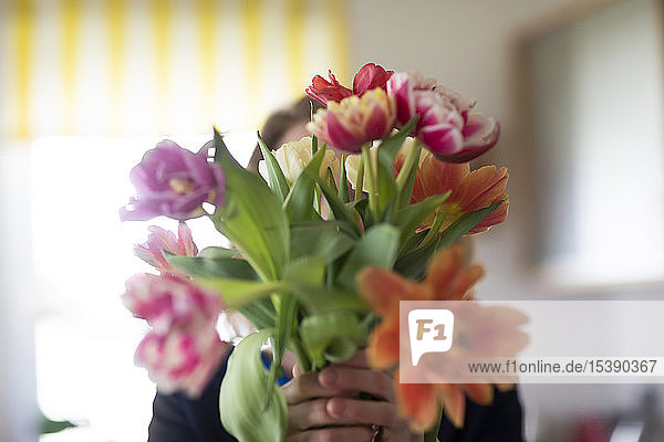 Woman hiding behind bunch of tulips