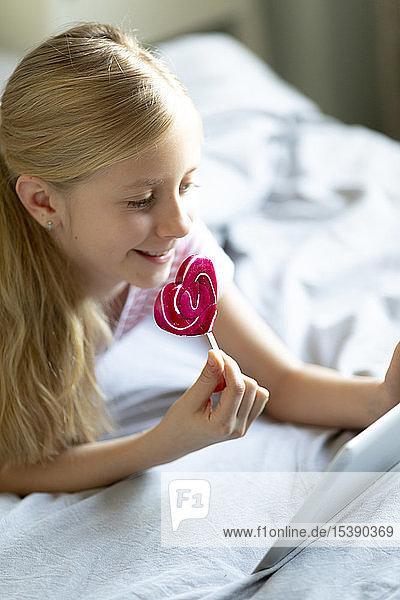Lächelndes blondes Mädchen liegt mit einem Lolli auf dem Bett und benutzt ein digitales Tablett