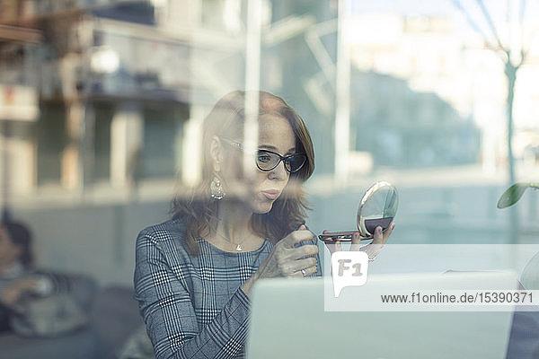 Reife Geschäftsfrau mit Kosmetikspiegel und Laptop in einem Cafe