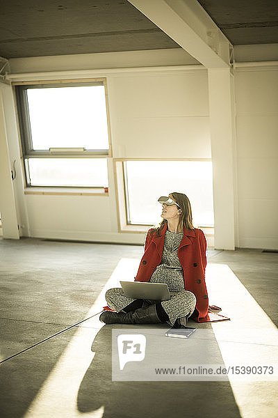 Pregnant busnesswoman sitting on floor of new office rooms  using VR goggles and laptop