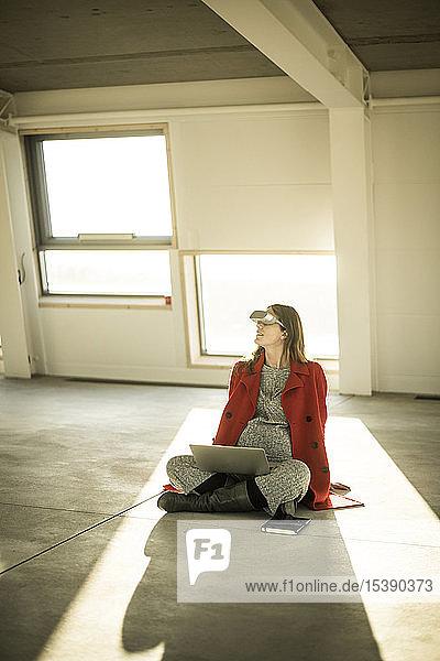 Schwangere Businessfrau sitzt auf dem Boden neuer Büroräume  benutzt VR-Brille und Laptop