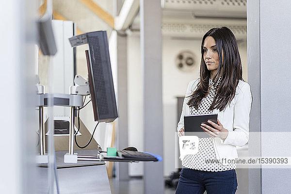 Porträt einer Geschäftsfrau mit Tablette in einer modernen Fabrik