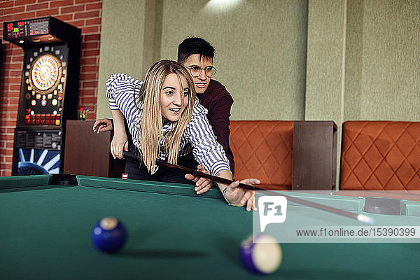 Young man guiding girlfriend at billiard table