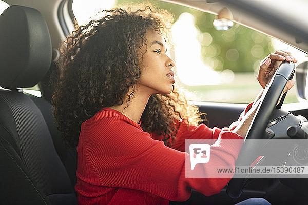 Beautiful young woman in driving car