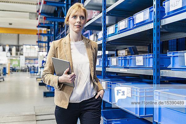 Geschäftsfrau mit Tablette in der Fabrik