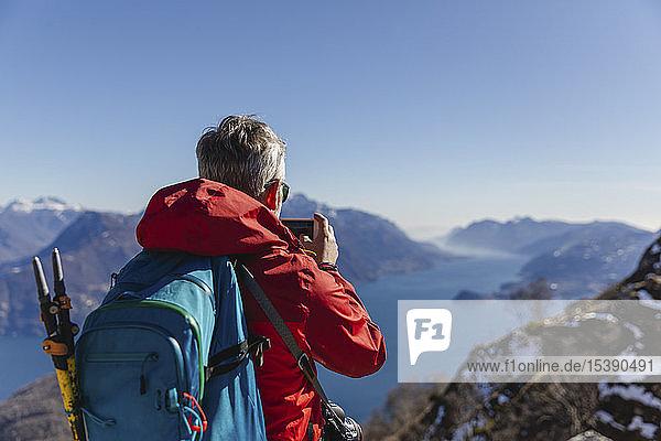 Italien  Como  Mann auf einer Wanderung in den Bergen über dem Comer See beim Fotografieren mit dem Handy