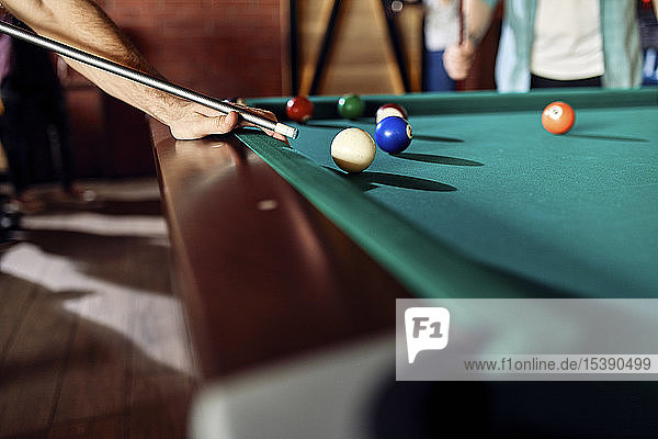 Close-up of man playing billiards