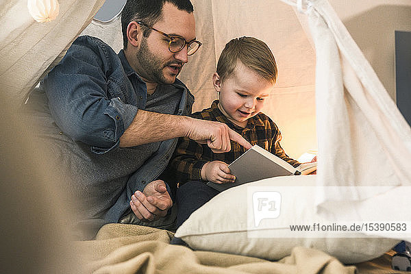 Father and son reading a book together in tent at home