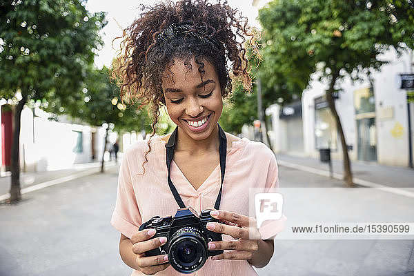 Smiling young woman looking at camera in the city