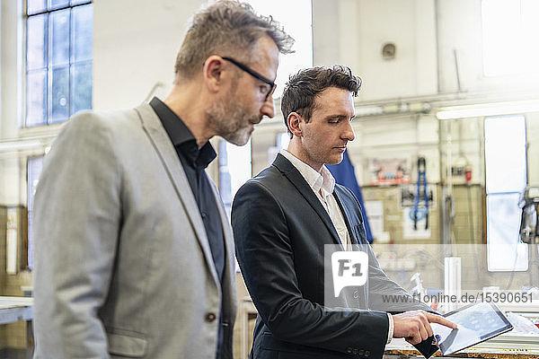 Zwei Geschäftsleute mit Tablette in einer Fabrik