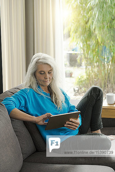 Portrait of mature woman sitting on the couch at home using digital tablet