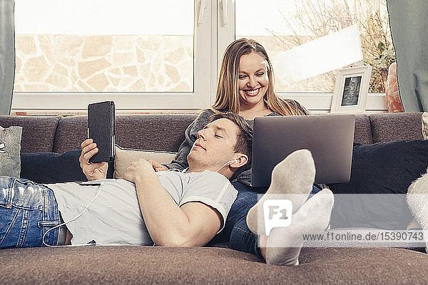 Junges Paar entspannt sich auf dem Sofa und nutzt Notebook  Smartphone und E-Book-Lesegerät
