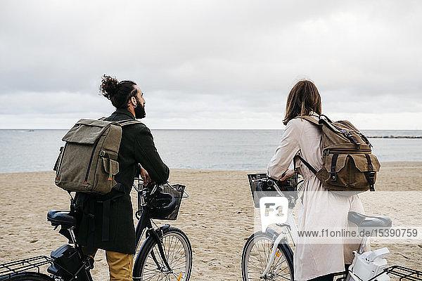 Paar mit E-Bikes am Strand mit Blick auf das Meer