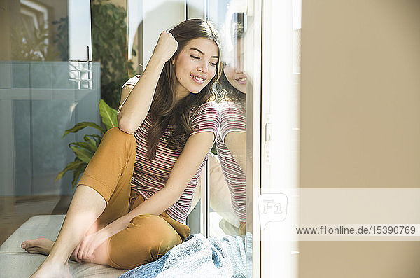 Smiling young woman sitting at home looking out of window