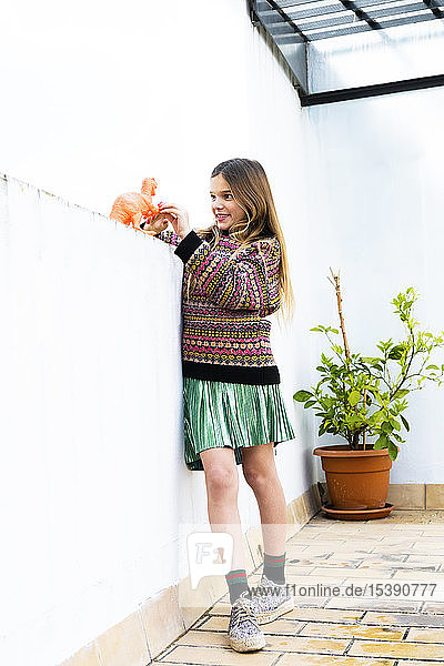 Girl playing with dinosaur toy at home