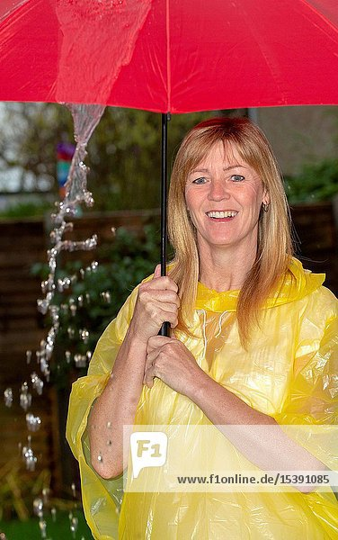 Woman wearing a yellow poncho holding a red umbrella in the rain