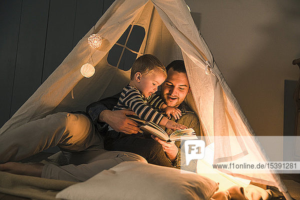 Father reading book to son at an illuminated tent at home