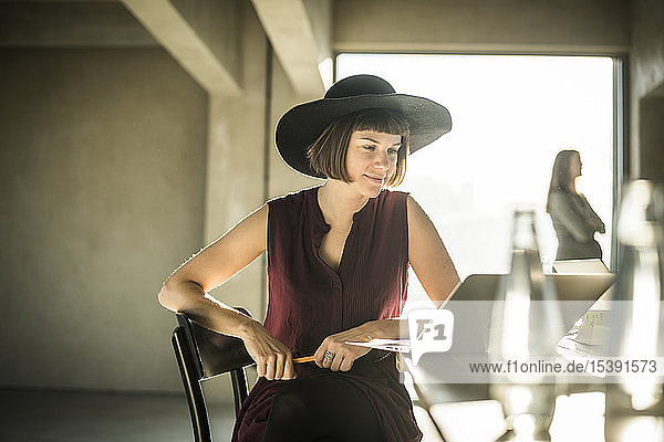 Woman with hat sitting in loft office  using laptop