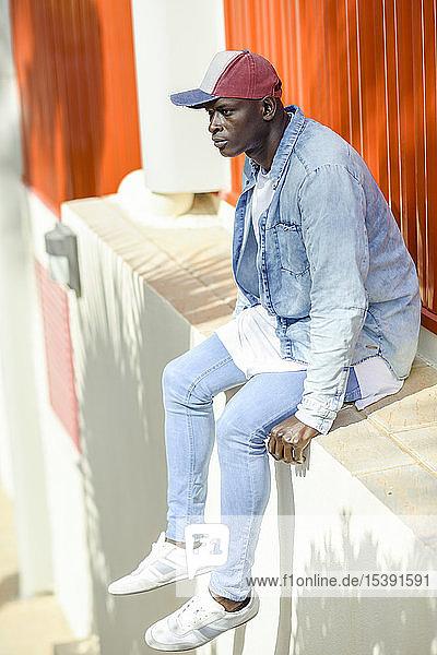 Mann in lässiger Jeansbekleidung und mit Baseballmütze an der Wand sitzend