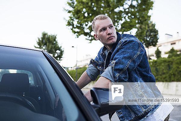 Junger Mann in Jeansjacke lehnt an Auto an