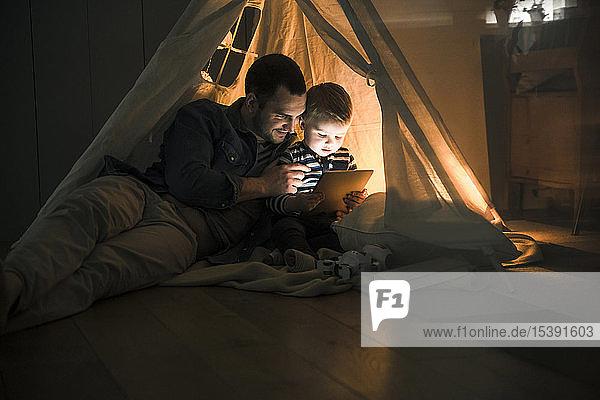 Vater und Sohn teilen sich eine Tafel in einem dunklen Zelt zu Hause