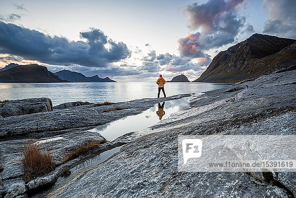 Norway  Lofoten Islands  Haukland Beach  hiker standing on rock