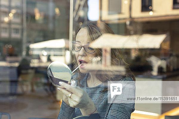 Reife Frau mit Schönheitsspiegel schminkt sich in einem Cafe
