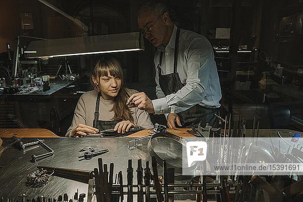 Kunsthandwerker und sein Mitarbeiter bei der Herstellung von Schmuck in seiner Werkstatt