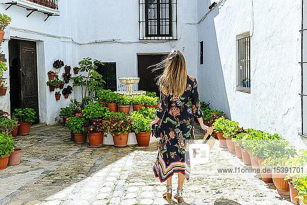 Spanien  Cádiz  Vejer de la Frontera  Rückenansicht einer modischen Frau  die im Innenhof steht