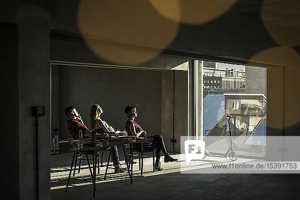 Group of creative professionals sitting in their office  looking out of the window  enjoying the sun