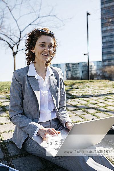 Geschäftsfrau in der Stadt  am Boden sitzend  am Laptop arbeitend
