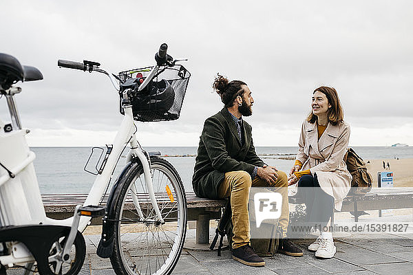 Couple sitting on a bench at beach promenade next to e-bike talking