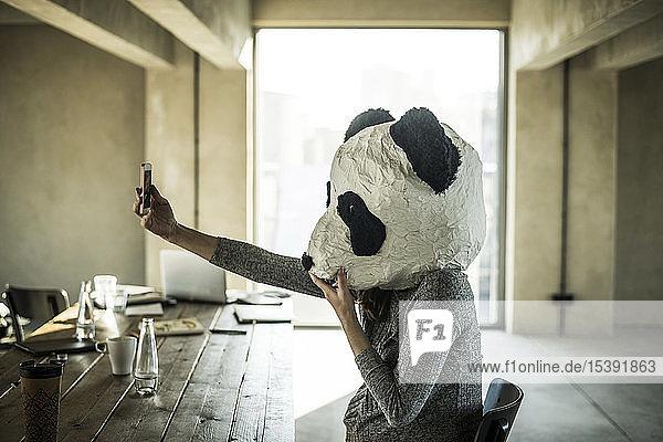 Woman with panda mask sitting in office  taking selfie