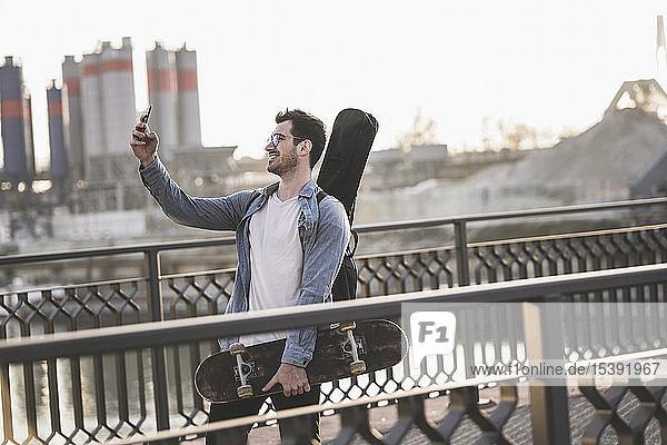 Junger Mann mit Gitarrenkoffer und Skateboard beim Selfie in der Stadt