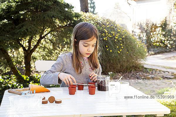 Porträt eines kleinen Mädchens am Gartentisch beim Säen von Samen