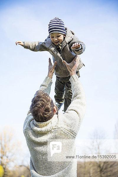 Vater wirft glücklichen Jungen unter blauem Himmel in die Luft