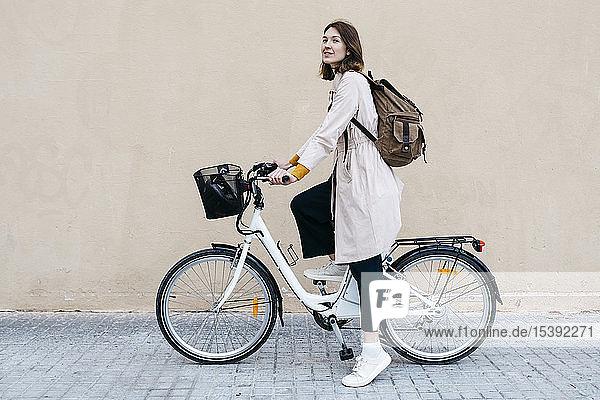 Frau mit E-Bike an einer Mauer