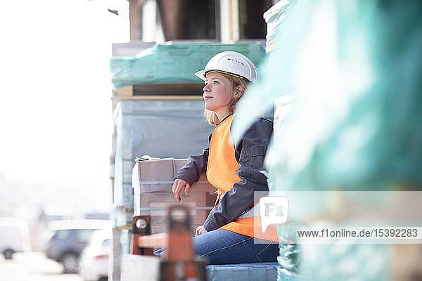 Frau mit reflektierender Weste und Schutzhelm auf Baumaterial sitzend