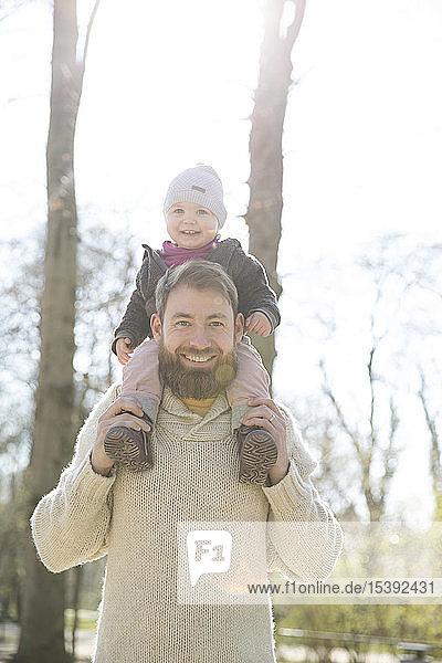 Porträt eines glücklichen Vaters  der seine Tochter im Park auf den Schultern trägt