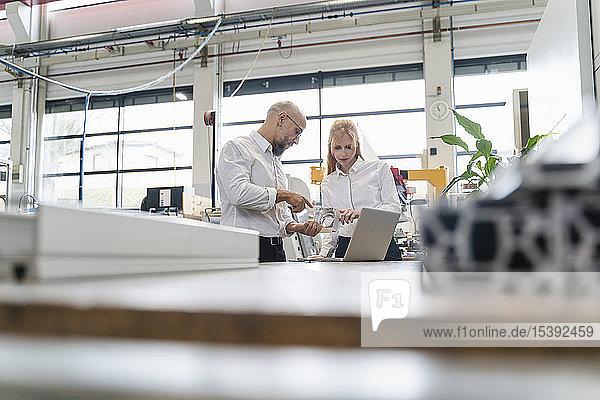 Geschäftsmann und Geschäftsfrau mit Laptop  der das Werkstück in der Fabrik untersucht