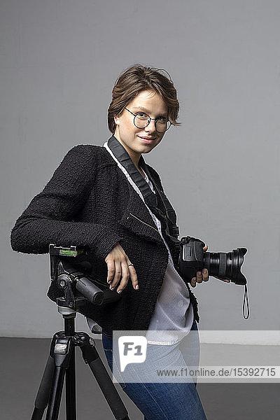 Porträt eines lächelnden jungen Fotografen mit Kamera und Stativ