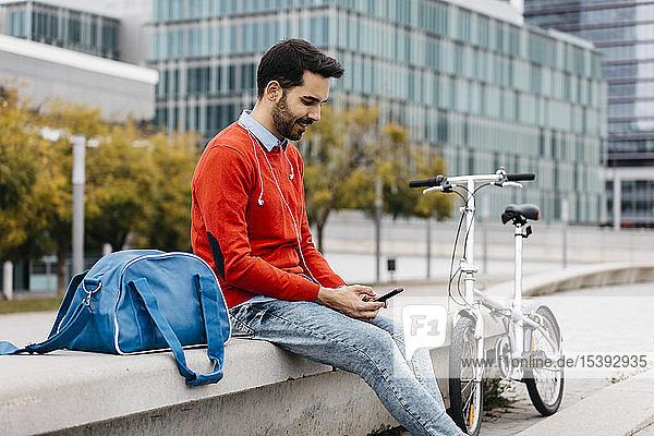 Lässiger Geschäftsmann  der auf einer Bank in der Stadt sitzt und sein Smartphone und seine Kopfhörer benutzt