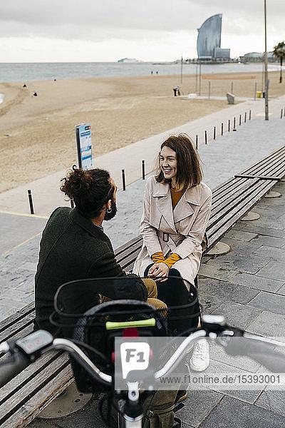 Ehepaar sitzt auf einer Bank an der Strandpromenade neben dem E-Bike und unterhält sich