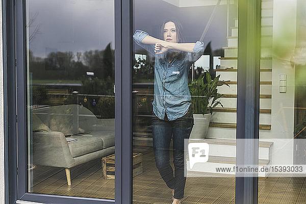 Seriöse Frau  die zu Hause hinter der Terrassentür steht