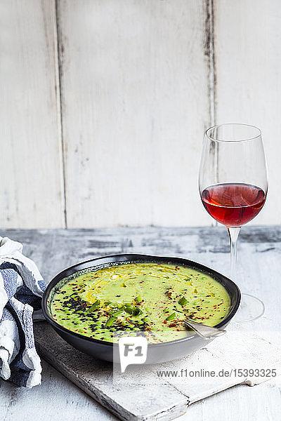 Schale mit frischer grüner Erbsensuppe mit Frühlingszwiebeln und einem Glas Rotwein