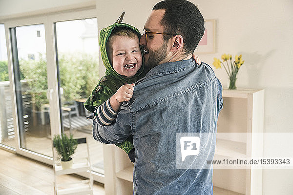 Father playing with happy son in a costume at home