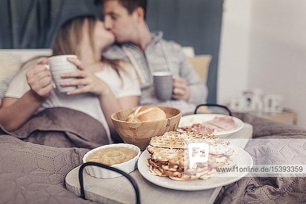Liebevolles junges Paar beim Frühstück im Bett