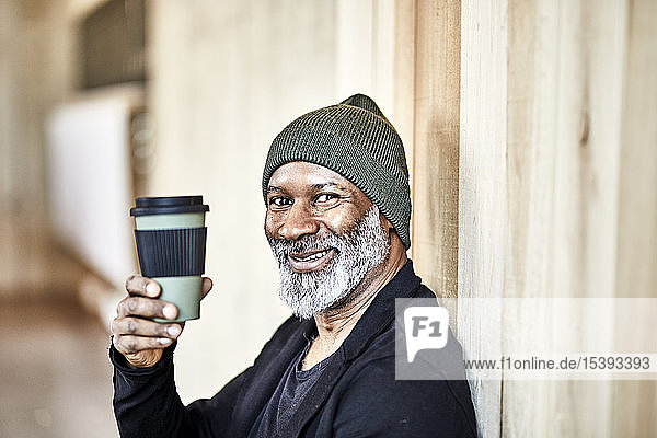 Portrait of happy mature businessman with takeaway coffee at wooden wall
