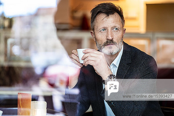 Portrait of mature businessman with cup of coffee in a cafe