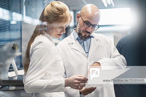 Zwei Techniker in Laborkitteln betrachten den Plan